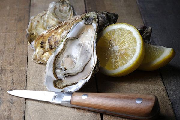 Un couteau à huîtres devant des huîtres et un citron