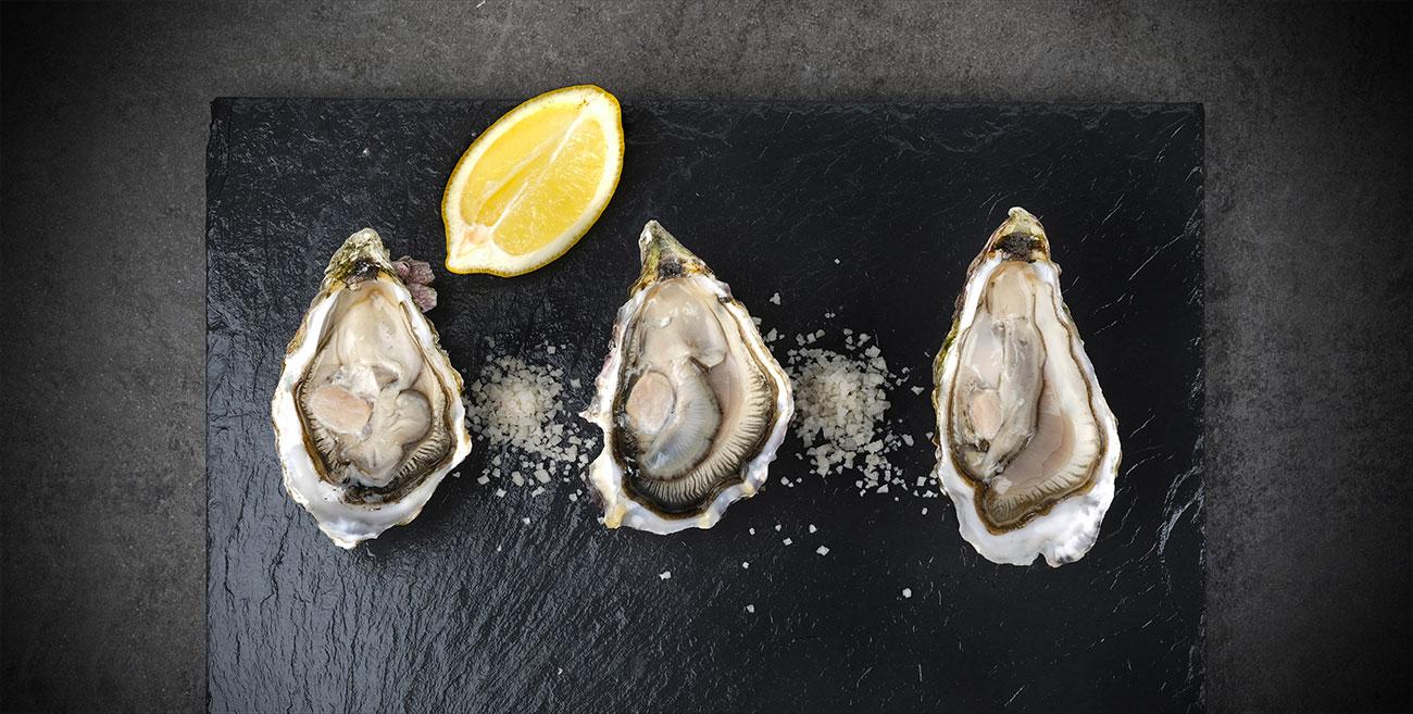 Trois huîtres et un citron sur une ardoise